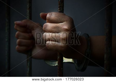 Human hand of prisoner on steel lattice close up.