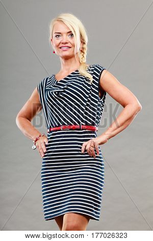 Mid adult blond attractive woman wearing striped dress posing studio shot on gray