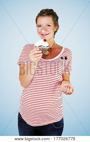 Smiling pregnant young woman wearing and red and white striped oversized T-shirt and maternity jeans is snacking on a large chocolate muffin with extra whipped cream and a cherry on top on blue background.
