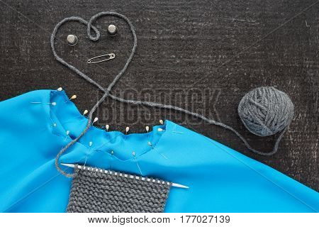 Grey knitting and blue needlework with pins and thimbles on black background.