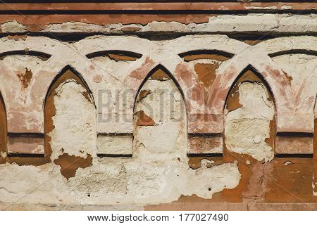 Old ruined wall with arches in bas relief