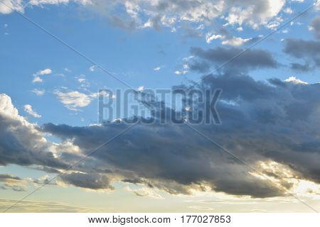 Cumulus colored clouds on blue and cream color sky near sunset.