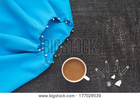 Blue needlework with pins and thimbles and a cup of coffee with milk on a black background.