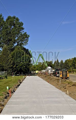 A freshly poured concrete sidewalk with a cement ready mix pumper truck in the distance at a construction site