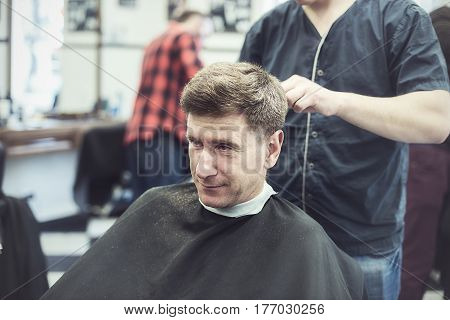 Satisfied, Confident Man In A Hairdressing Salon Enjoys The Process Of Its Haircuts