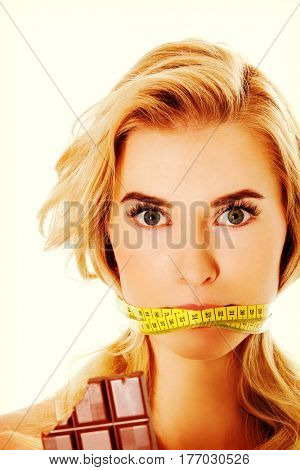 Woman with tied mouth holding bar of chocolate