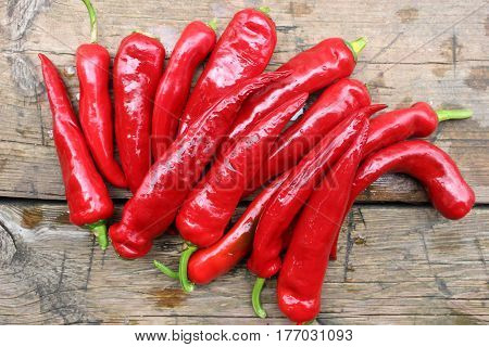 Photo close-up of a pile of chilli pepper pods of red color on a wooden background