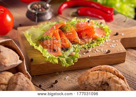 Slices of smoked salmon with dill chili pepper tomatoes and bread on rustic wooden background.