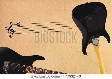 Stave and black electric rock guitar and back of guitar body on the rough cardboard background.