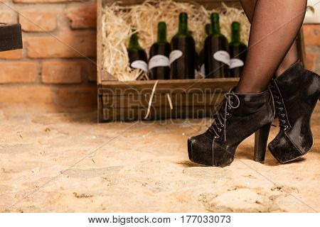 Female Legs And Wine Bottles In Cellar