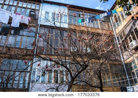 A typical georgian yard of an old traditional wooden house with persimmon tree and clothes and linen drying on the ropes.