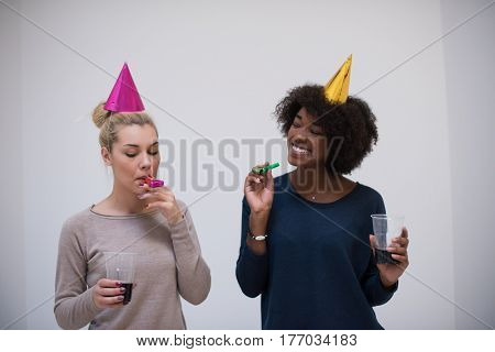 people and celebration concept  young multiethnics smiling women in party caps blowing to whistles