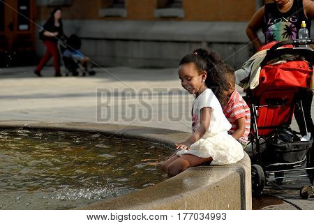 Oslo Norway - July 22 2014: Adorable child having fun by a city fountain on hot and sunny summer day the Royal Palace in Oslo.