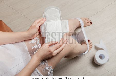 Crop photo of barefoot female holding female's hygiene means.