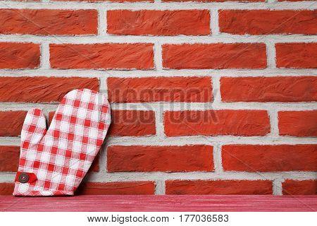 Kitchen Potholder On A Brick Wall Background