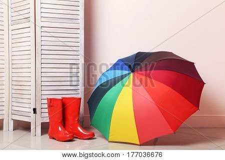 Red Boots With Umbrella Near Wooden Folding Screen On A Beige Background