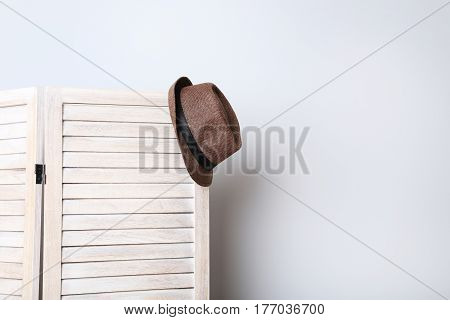 Hat Hanging On Wooden Folding Screen On A Grey Background
