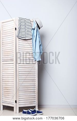 Clothes Hanging On Folding Screen On A Grey Background