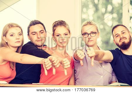Team of friends college students giving thumb down gesture