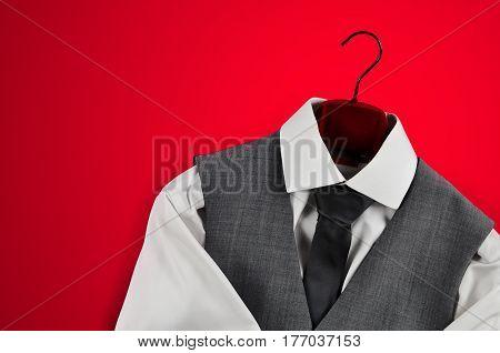 Men´s elegant grey waistcoat, tie and white shirt on a red velvet clothes hanger in bottom right corner on red background.