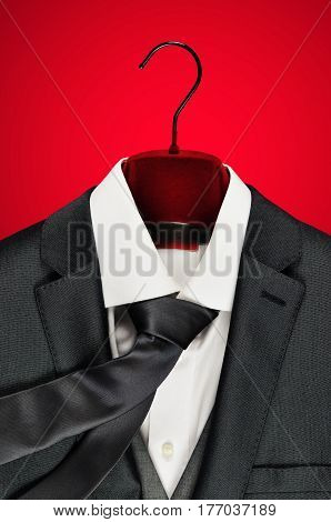 Close-up of men´s elegant grey suit and white shirt on a red velvet clothes hanger on red background.