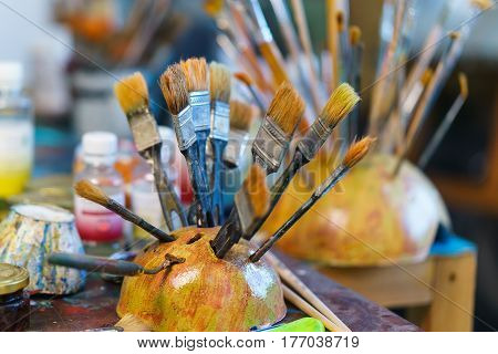 artist brushes in the stand on blurred background.