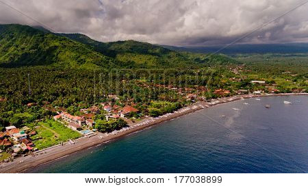 The tropical bay with stony beach boats and buildings aerial view. Village of Amed Bali Indonesia.