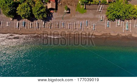 Top view of the water coast line with stony beach with boats. Village of Amed Bali Indonesia.
