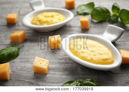 Gravy boats with tasty cheese sauce and basil on wooden background