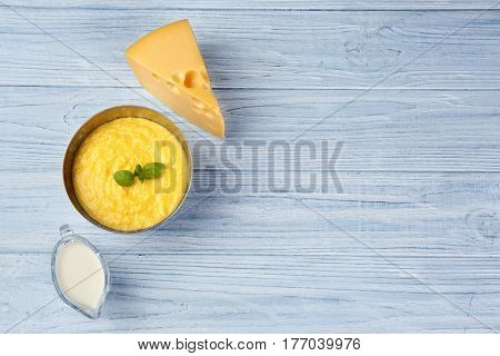 Bowl with tasty cheese sauce and gravy boat with milk on wooden background
