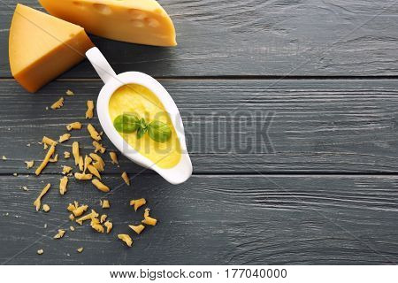 Gravy boat with tasty cheese sauce on wooden background