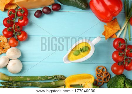 Gravy boat with cheese sauce and different products on color wooden background