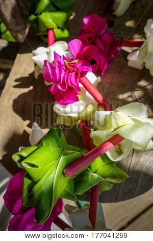 Traditional polynesian flower necklace on a wooden background