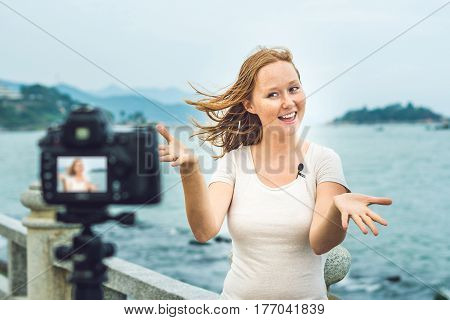 A Young Woman Blogger Leads Her Video Blog In Front Of A Camera By The Sea. Blogger Concept