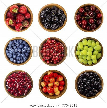 Collage of different fruits and berries isolated on white. Blueberries cherries blackberries grapes strawberries currants. Collection of fruits and berries in a bowl. Top view.