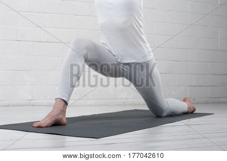 Cropped shot of fit girl practicing yoga against white wall. young woman exercising indoors