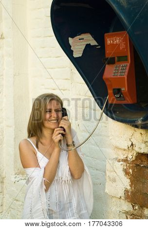 A girl in white clothes laughs and communicates cheerfully on a street payphone.