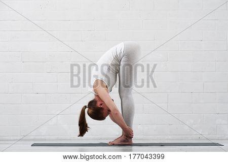 Yoga woman practicing indoors. Fit girl wearing white sportswear exercising on grey mat.