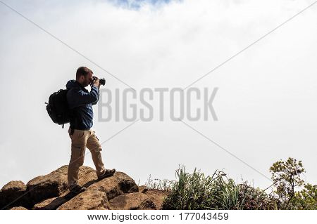 Hiker or photographer with DSLR camera is standing on the edge of abyss above vast forest territory of foggy mountains in Sri Lanka