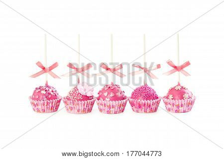 Five romantic pop cake with pink frosting decorative sprinkles and pink ribbons isolated on white background.
