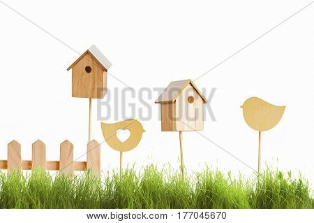 birdhouses and wooden bird on a background of green grass. Easter concept.