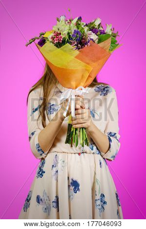 Beautiful Girl In Dress Holding A Bouquet Of Different Flowers. Covering Her Face With A Bouquet Of