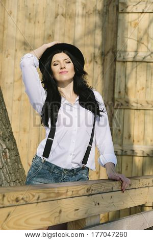 Portrait of young happy farmer hipster woman looking at camera on wooden background. Real people concept.