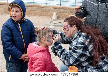 Participant Of Festival Drawing Butterfly On The Girl's Face
