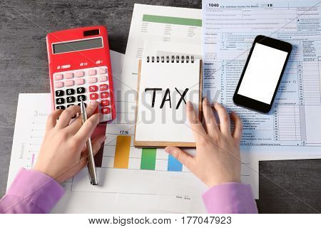 Word TAX on paper sheet and female hands working with documents at table