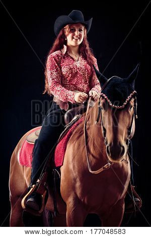 Cowgirl With Her Horse. Studio shot on black background.