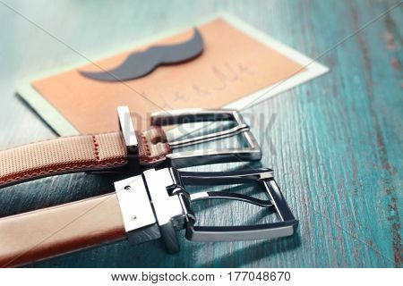 Leather belts and card on color wooden background