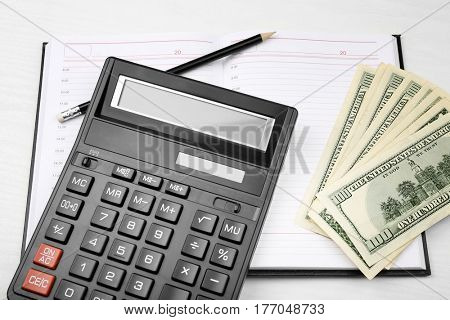 Calculator, notebook and money on table