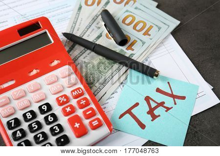 Calculator with documents and money on table. Tax concept