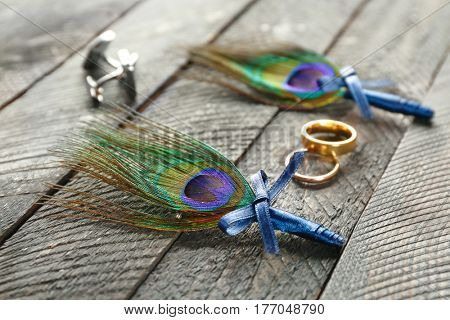 Wedding rings, cuff-links and boutonnieres with peacock feather on wooden table